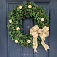 blue front door with neutral boxwood wreath