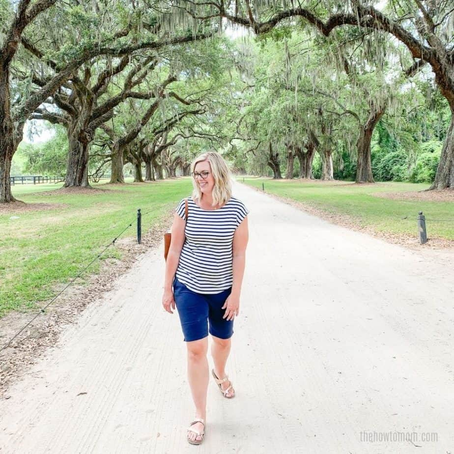 woman wearing knee length shorts under canopy of southern oak trees.