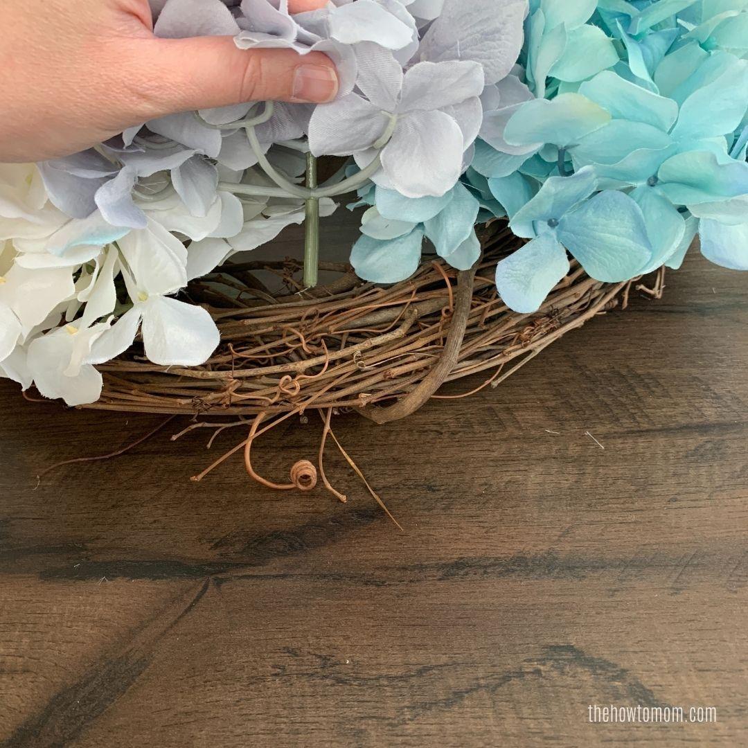 shoving hudrangea blooms onto grapevine wreath